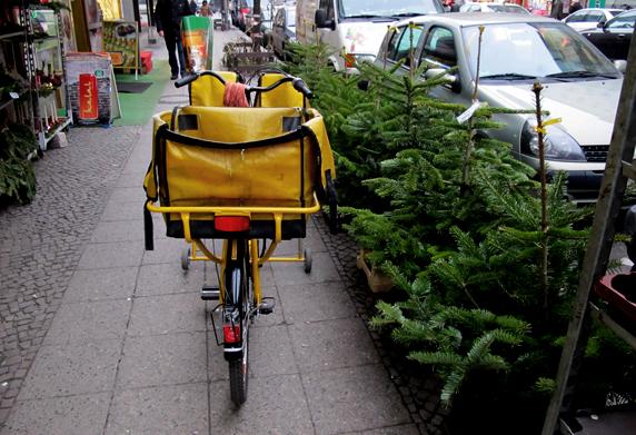 Postfahrrad neben Weihnachtsbäumen