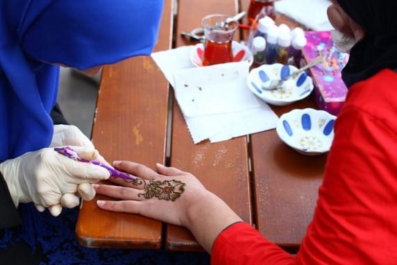 Eine Frau bemalt die Hand eines Mädchens.