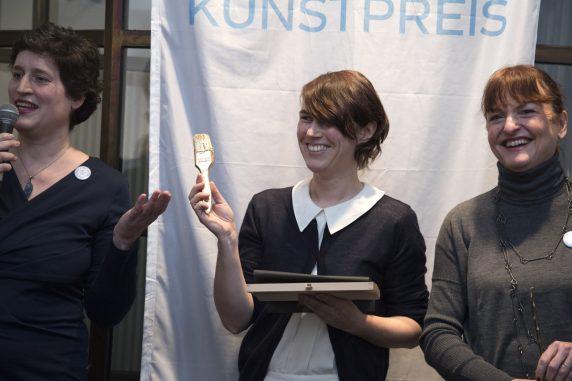 Die Gewinnerin des Hauptpreises, Diana Artus, mit einem von Künstlerin Barbara Duisberg gestalteten goldenen Pinsel bei der Verleihung neben Katharina Bieler, Leiterin des Fachbereichs Kultur des Bezirksamtes Neukölln (l.) und Anne Keilholz, Geschäftsführerin von STADT UND LAND