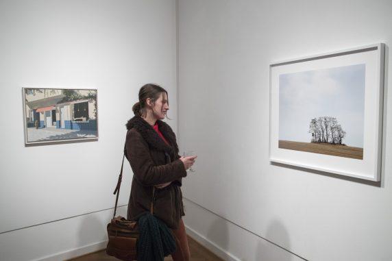 """Ausstellungsbesucherin vor Carsten Kaufholds """"Straße 46"""" und Franca Wohlts """"Umland"""""""