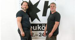 """Thorsten Schlenger (li) und Martin Steffens vor dem neuen Logo der """"48 Stunden Neukölln"""". Foto: Florin Leontis"""
